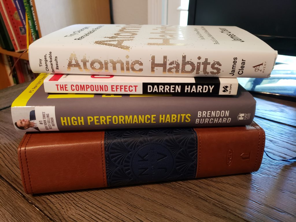 stack of books with atomic habits on top